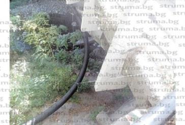 ЧИТАТЕЛИ СИГНАЛИЗИРАТ: Водопроводът за минерална вода към хотела на съветника Р. Калайджиев виси на въженца под моста за Бачиново, предпазният парапет е счупен…